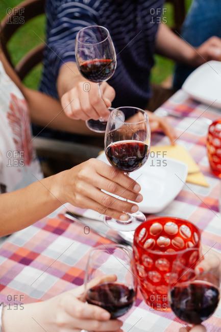 People raising glasses of red wine