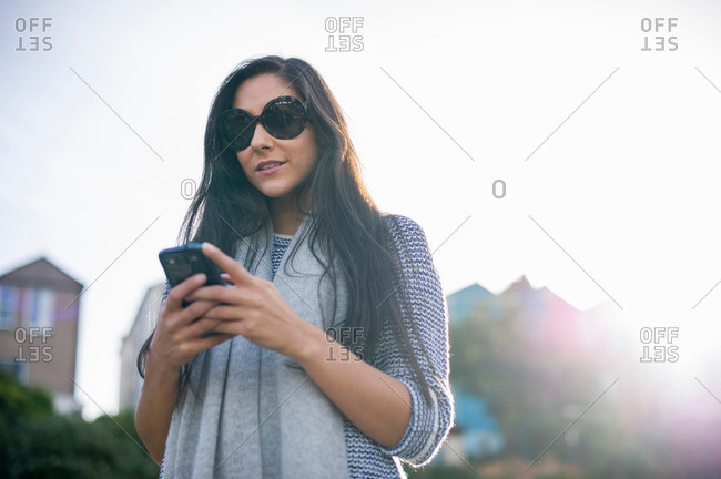 Young woman wearing sunglasses using smartphone