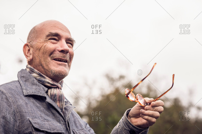 Senior man gesturing with spectacles