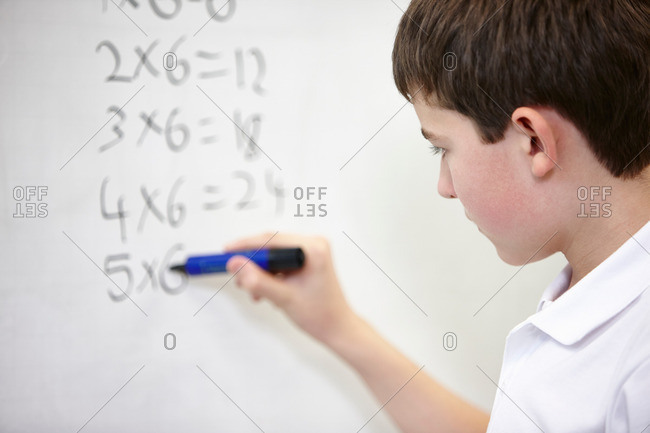 Close up of schoolboy doing multiplication on white board