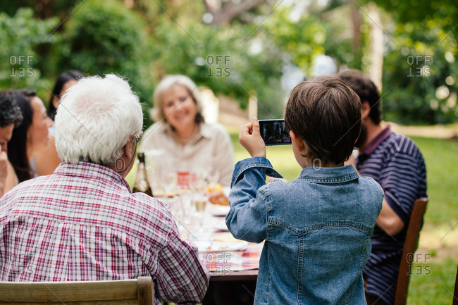 Boy photographing family at outdoor meal