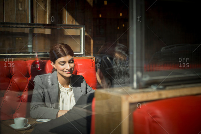 Couple sitting across from one another in restaurant booth