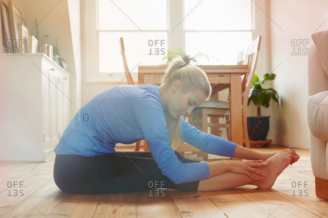 Young woman sitting on floor leaning forwards touching toes