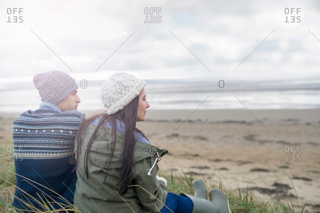 Young couple sitting on beach, Brean Sands, Somerset, England