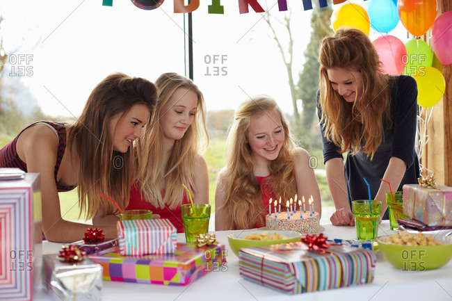 Teenage girl sharing birthday cake with friends
