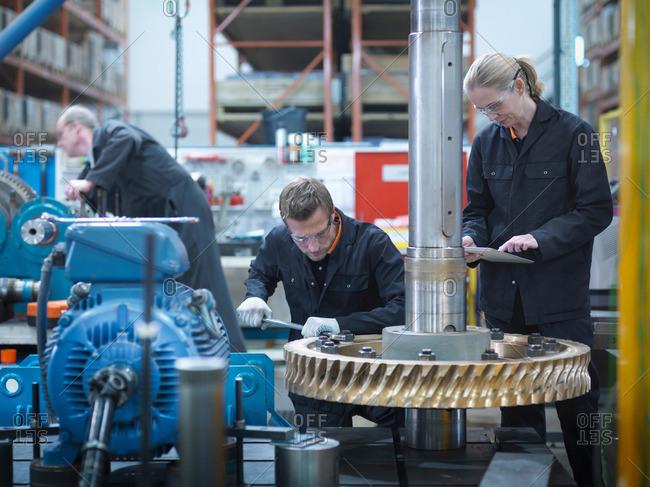 Engineers assembling industrial gearbox in an engineering factory