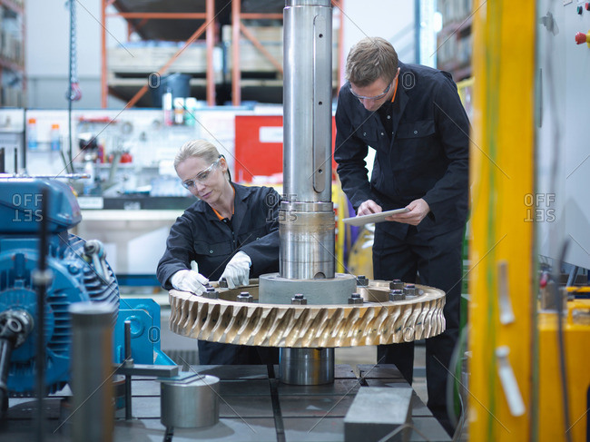 Engineers assembling industrial gearbox in a factory