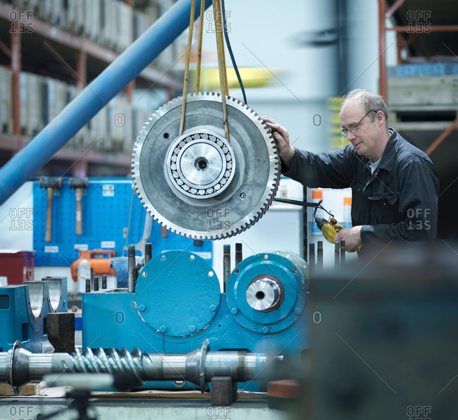 Engineer assembling industrial gearbox in a factory