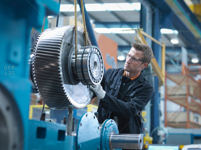 Engineer assembling industrial gearbox in an engineering factory