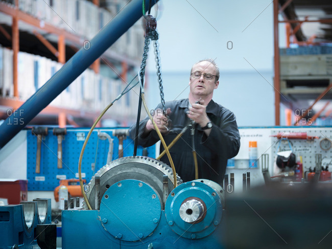 Engineer putting together an industrial gearbox in an engineering factory