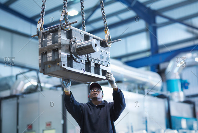 Man using crane to move industrial gearbox to paint works in engineering factory