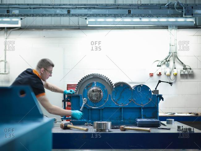 Man assembling industrial gearbox in engineering factory