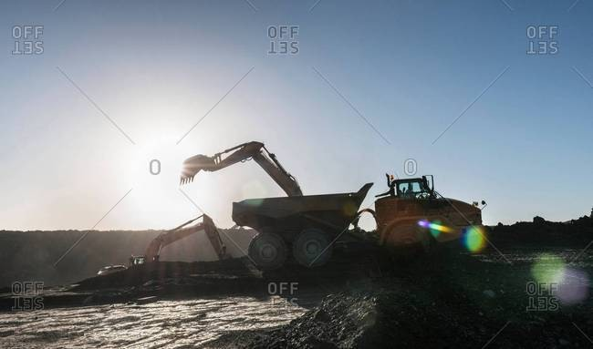 Silhouette of digger and dumper truck loading coal in surface coal mine