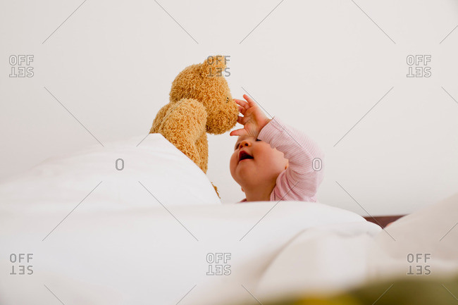 Baby girl fascinated with teddy bear
