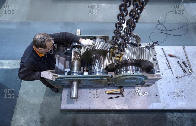 Overhead view of engineer repairing industrial gearbox in factory