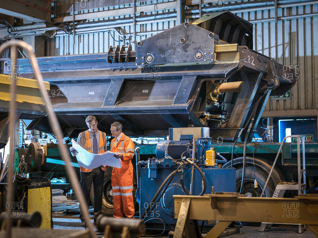 Engineers inspecting engineering drawings together