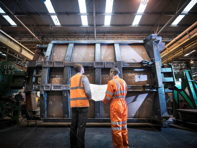 Engineers inspecting engineering drawings in factory, rear view