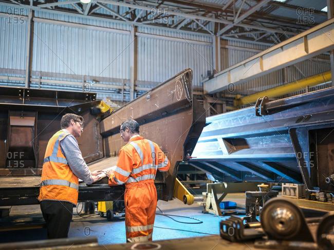 Engineers discussing engineering drawings in factory