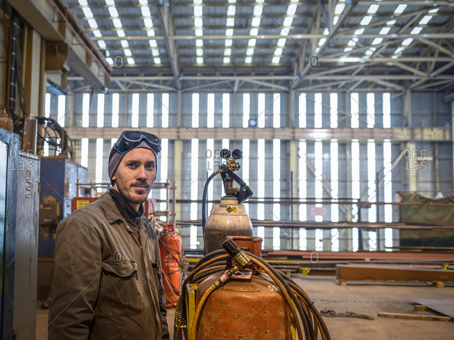 Portrait of welder wearing overalls and safety goggles in factory