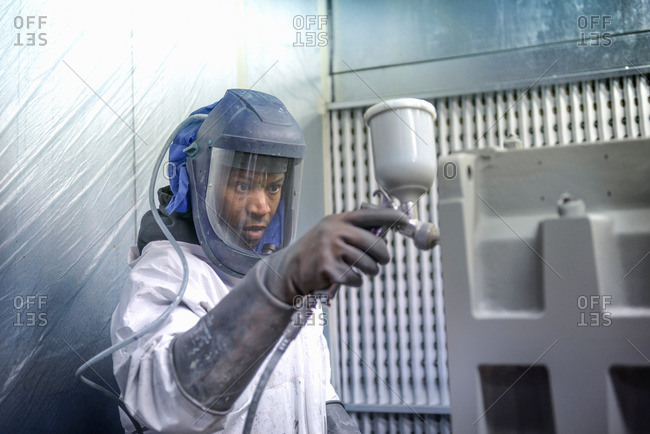 Worker paint spraying industrial gearboxes