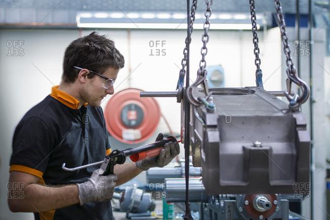 Apprentice engineer applying sealant to industrial gearbox in factory