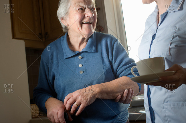 Personal care assistant carrying cup of tea for senior woman