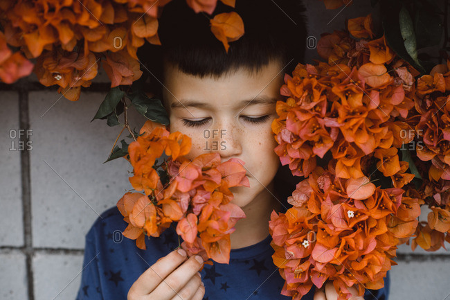Portrait of a boy standing against a wall surrounded by orange flowers