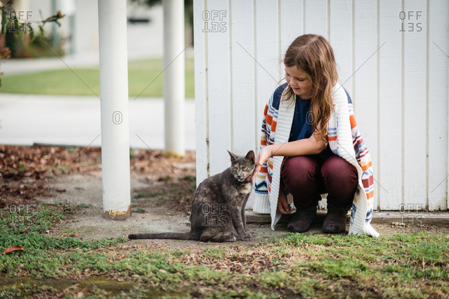 Girl kneeling next to a cat outside near a fence