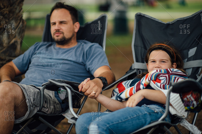 Father and daughter sitting in lawn chairs holding hands