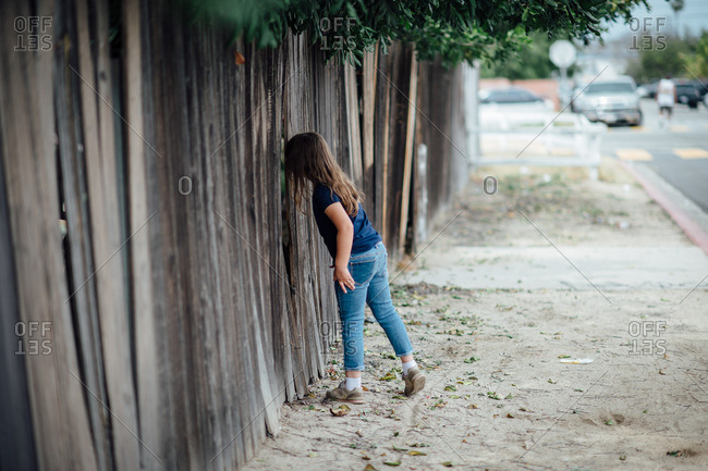 Girl looking through the slats of a wood fence