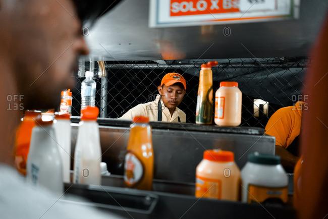 Caracas, Venezuela - December 26, 2015: Man preparing food in street food stand