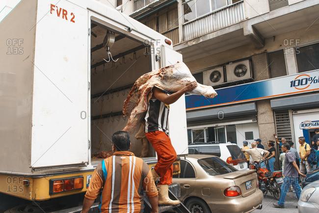Caracas, Venezuela - December 27, 2015: Man carries piece of meat down truck while other man checks truck