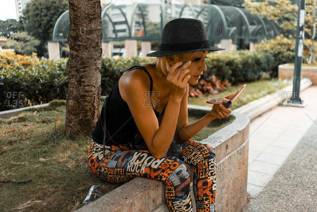Caracas, Venezuela - January 3, 2016: Girl puts on make-up in a public park