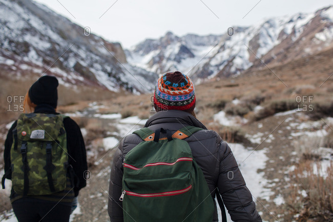A pair of hikers walking along a mountain trail