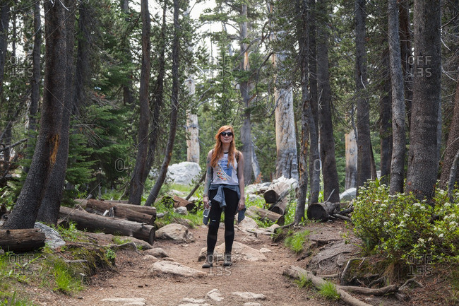 Portrait of a woman standing along a woodland hiking trail