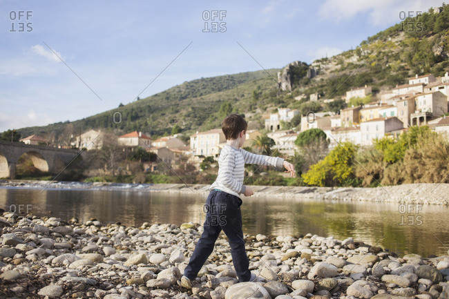 Boy throwing rocks in the water