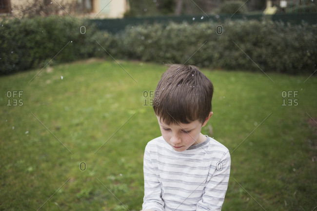 Boy standing outside while snowflakes fall