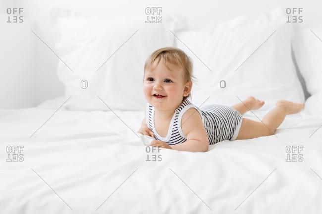 Baby lying on tummy on white bed