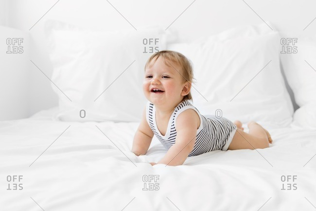 Baby on tummy on white bed