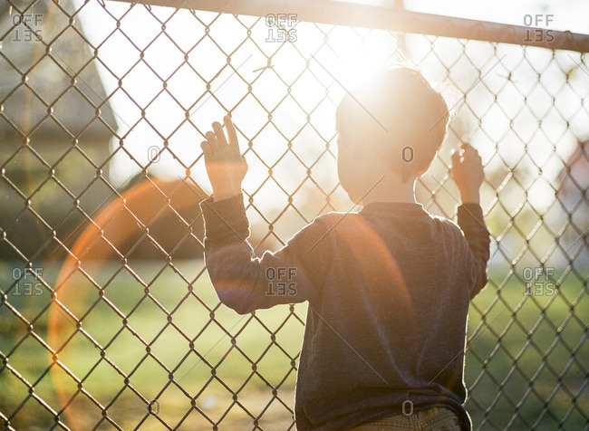 Boy at a chain link fence