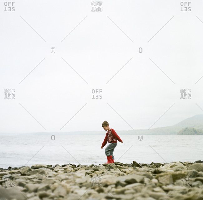 Boy walking on shore rocks