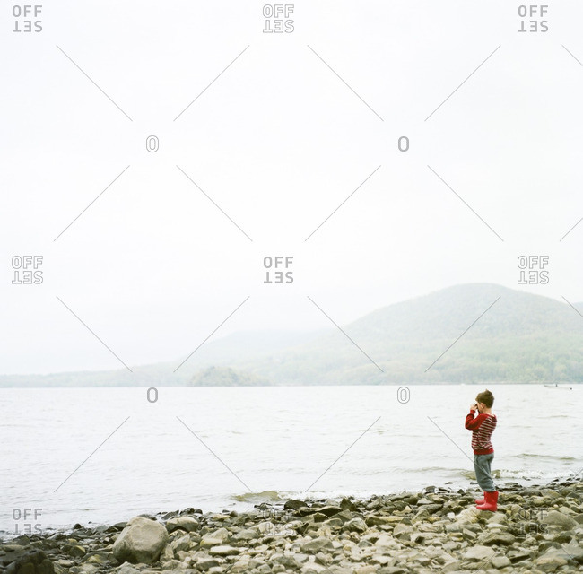 Boy taking picture on shore