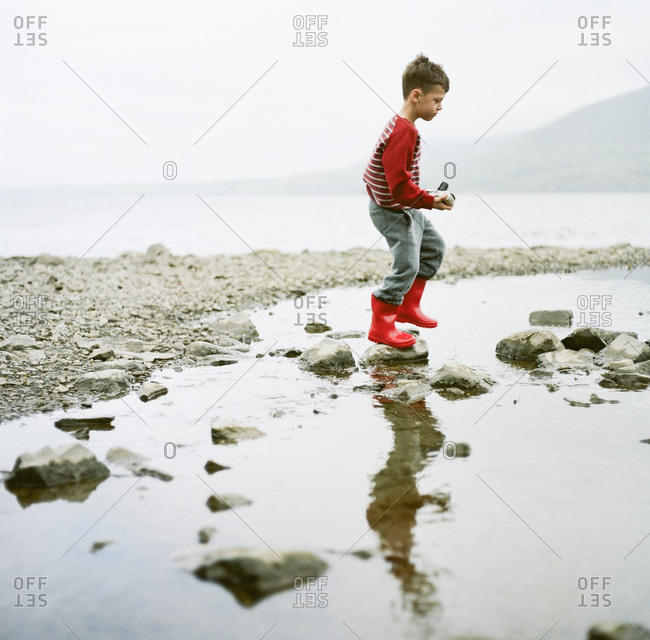 Boy walking on shore with camera
