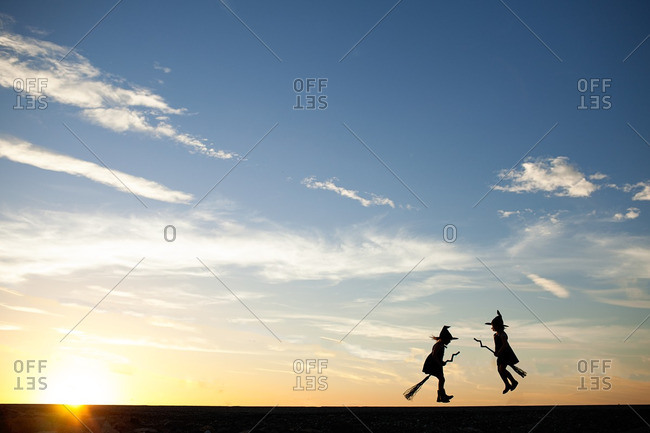 Silhouetted girls in witch costume