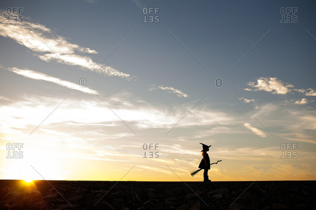 Silhouetted girl in witch costume