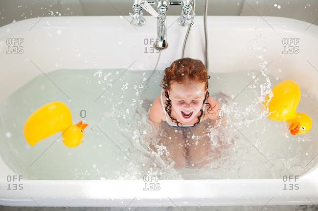 Girl laughing in tub with toys