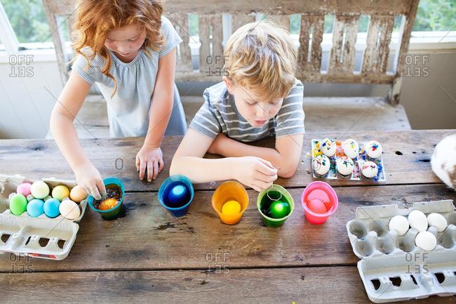 Kids dip dying Easter eggs