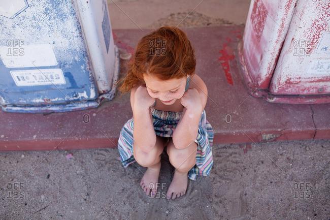 Barefoot girl on concrete ledge