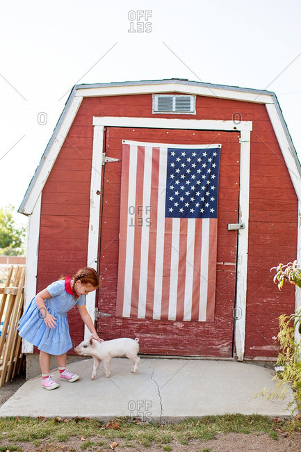 Girl petting pig by flag