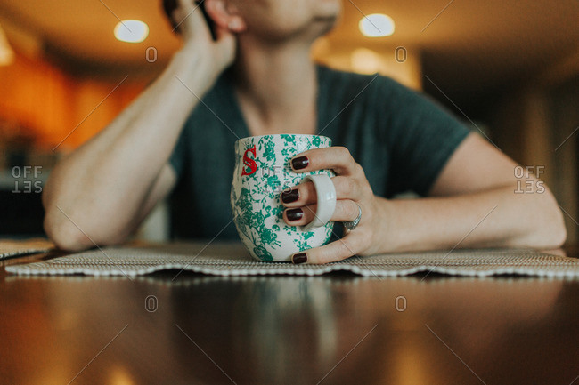 Close-up of person sitting at a table with a coffee mug